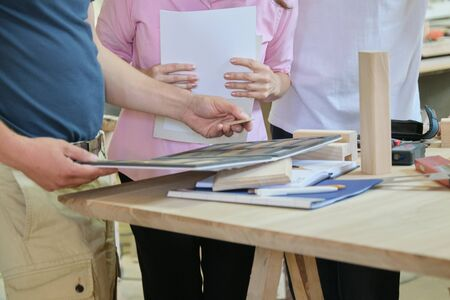 Group of people designer, client, carpenter, engineer choosing wooden products, working discussion, background carpentry workshop. Stockfoto