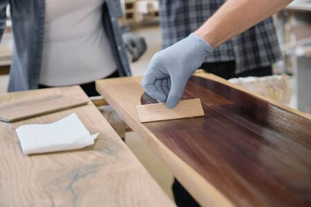 Closeup of workers hand covering wooden plank with finishing protective cover for wood, carpentry furniture woodworking production Zdjęcie Seryjne