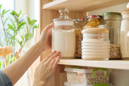 Food products in the kitchen storing ingredients in pantry. Woman taking jar of flour