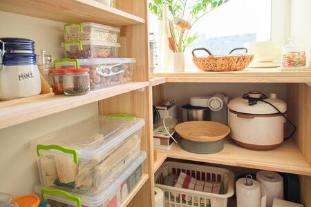 Wooden shelves with food and utensils, kitchen appliances in the pantry.