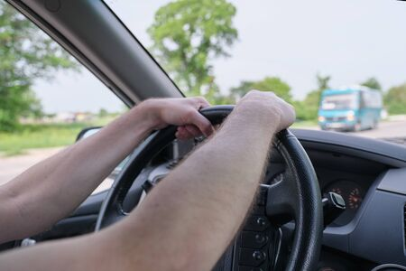 Drivers men hands on steering wheel, day time Archivio Fotografico