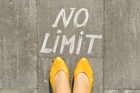 No limit text on gray sidewalk with woman legs, top view.