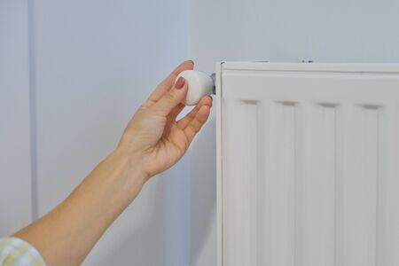 Hand on heating radiator regulates the temperature with thermostat regulator.