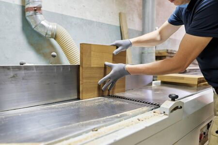 Male carpenter using machine in woodworking woodshop, worker grinds wooden pieces for furniture.