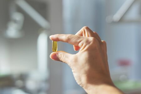 Yellow gel capsule of vitamin D, E, omega-3 in womans hand close-up, dental office background. Care, health, healthy nutrition