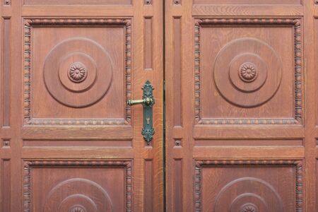 Detail of brown carved entrance double door, door handle close-up. Archivio Fotografico