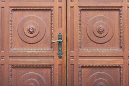 Detail of brown carved entrance double door, door handle close-up.