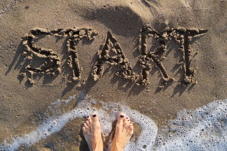 Text start written in sand on sea beach and womans bare feet standing in front of the word Banque d'images