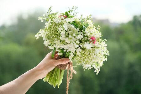 Close-up bouquet of fresh flowers rose and lily of the valley in woman hand. Springtime, holidays, wedding, beauty