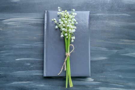 Small bouquet of lilies of the valley with craft rope on notebook, book, gray background, top view