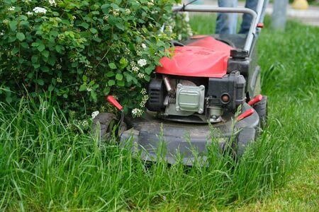 Working lawn mower on green lawn with trimmed grass.