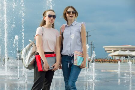Outdoor portrait of young girls student with backpacks, books are sitting near the city fountain, talking, learning Standard-Bild