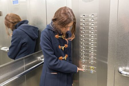 Young teen girl in elevator, presses the elevator button.