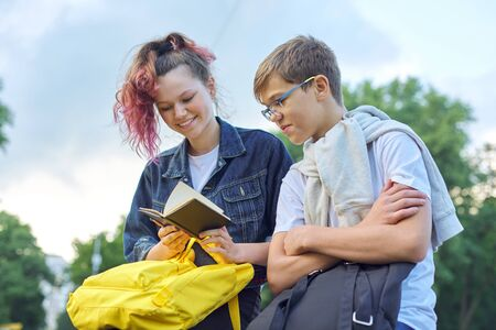 Outdoor portrait of two talking teenagers, students boy and girl with notepad, back to school