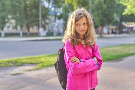 Portrait of school girl nine years old in jacket with backpack. Smiling child outdoors posing with folded arms
