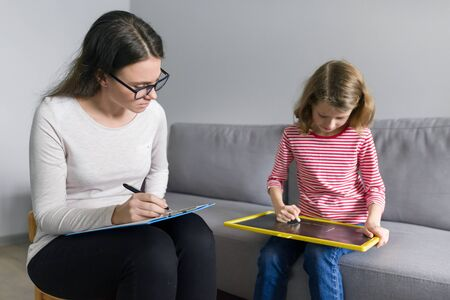 Professional child psychologist talking with child girl in office, children problems, mental professional help