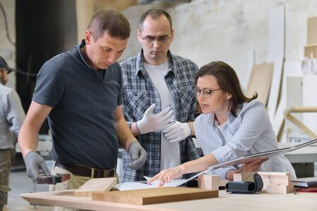 Équipe d'ouvriers de l'atelier de menuiserie discutant d'un projet de mobilier avec un client, un designer, un ingénieur. Groupe de personnes dans l'atelier de menuiserie