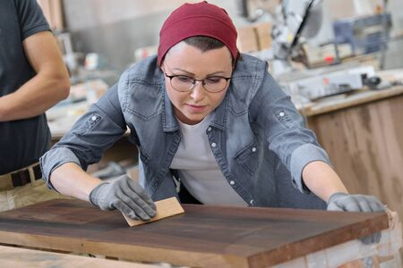 Mature craftswoman working in woodshop. Female painting wooden board with oil, varnish. Furniture joinery wood business.