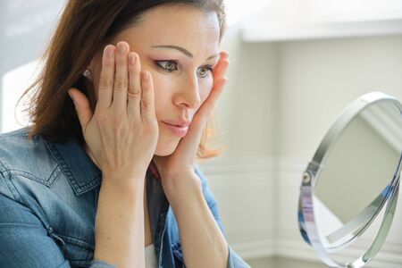 Portrait of mature woman with make-up mirror massaging her face, beautiful female 40 years old sitting at home at table