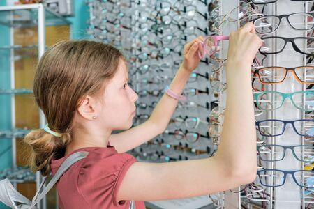 Little buyer in the glasses store, girl child chooses glasses. Standard-Bild