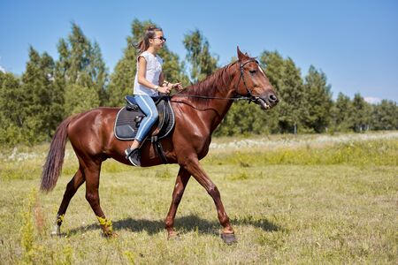 Teenager girl riding a brown horse, horseback riding for people in the park. Stock Photo