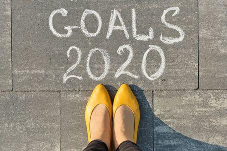 2020 goals, written on gray sidewalk with woman legs in, top view.