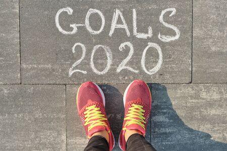 2020 goals, written on gray sidewalk with woman legs in sneakers, top view. Standard-Bild