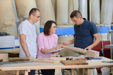 Group of working people discussing work process, wood products in carpentry workshop.