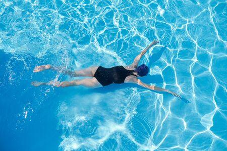 Jeune femme nageant sous l'eau dans une piscine extérieure, vue de dessus du dos de la fille, mode de vie sain et actif des jeunes Banque d'images