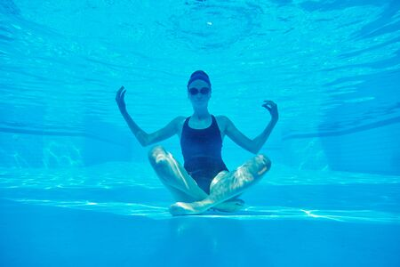 Young athletic woman sitting in lotus pose underwater in swimming pool.