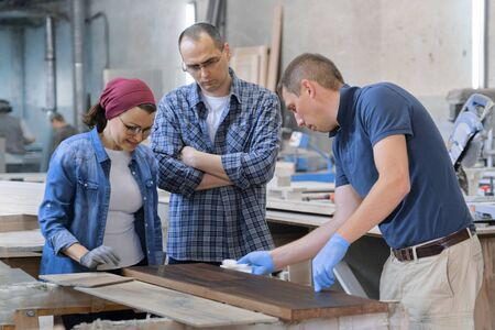 Workers in carpentry woodworking workshop, varnishing wooden plank with oil. Stock Photo