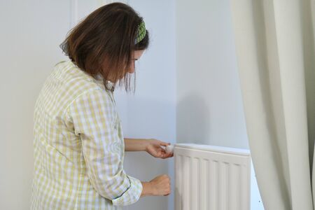 Woman near heating radiator in home interior, regulates the temperature with thermostat regulator.