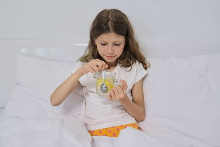 Smiling little girl holding a glass of natural homemade drink with lemon sitting in home white bed.