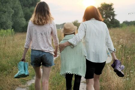 Family mother and two daughters walking together along country road after summer rain holding rubber boots in hands, back view, nature background golden hour