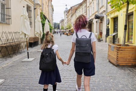 Children going to school, two girls sisters teenager and elementary school student with backpacks walking together, holding hands, back view Zdjęcie Seryjne