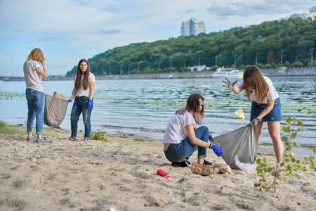 Teenagers cleaning plastic trash in nature, riverbank. Girls in gloves with trash bags. Environmental protection, youth, volunteering, charity, and ecology concept