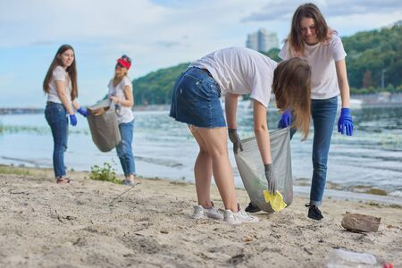 Group of students with teacher in nature doing cleaning of plastic garbage. Environmental protection, youth, volunteering, charity, and ecology concept Banque d'images