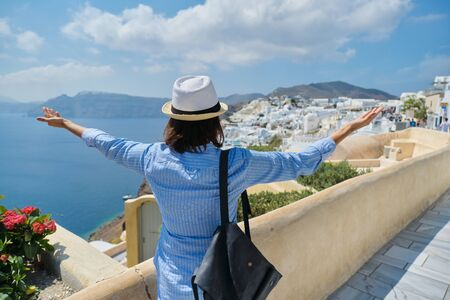 Happy woman tourist with arms raised up, emotion of freedom success happiness. Rear view of female with hat backpack, landscape of Greek island Santorini, Oia Standard-Bild