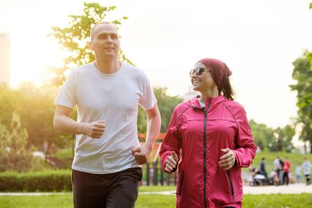 Running smiling mature couple outdoor, sport active lifestyle in middle-aged people.