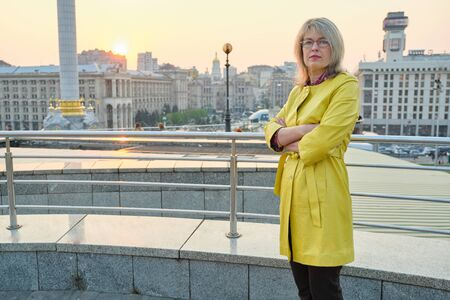 Outdoor portrait of confident mature woman with folded hands. Beautiful smiling age woman with glasses, arms crossed, background city panorama, copy space