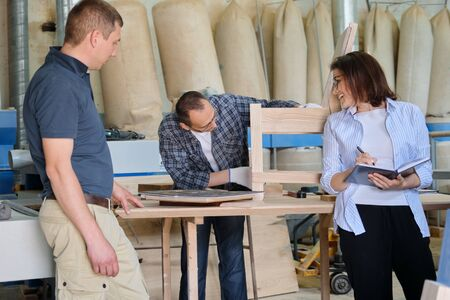 People working in carpentry workshop, woman and men workers making sample of wooden chair using design drawing