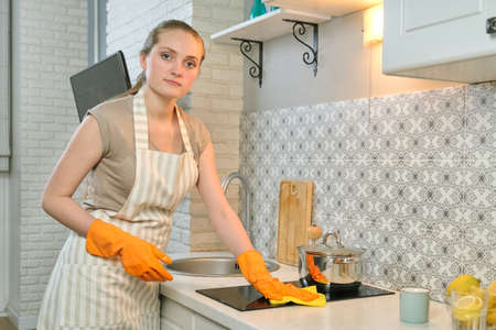 Young woman in apron gloves cleaning the kitchen after cooking, female washing hob with rag Standard-Bild