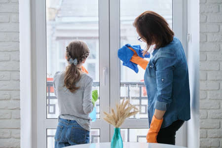 Mother and daughter child in rubber gloves with detergent and rag washing windows together. Girl helping woman do house cleaning Standard-Bild