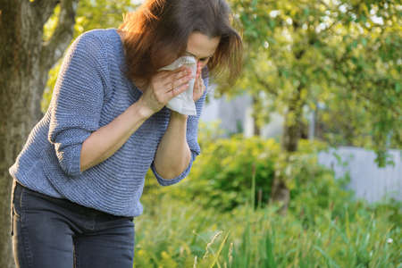 Mature woman sneezing in handkerchief, background green nature outdoor, allergy to pollen, colds, copy space