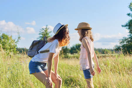 Happy children two girls sisters teenager and younger laughing and having fun in meadow, blue sky, summer nature. Active healthy lifestyle, friendly family, happy childhood, copy space