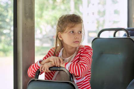 Child passenger of city bus, trolleybus, girl sitting in the passenger seat Standard-Bild