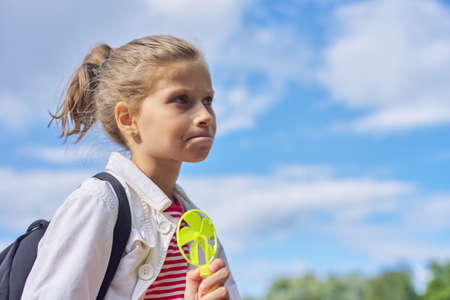 Girl child blonde 9, 10 years old in profile, head closeup, sky in clouds background, copy space Banco de Imagens
