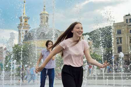 Teenage girls, people having fun in the city fountain, splashing, wet clothes, positive emotions Standard-Bild