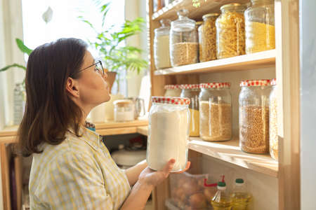 Food storage, wooden shelf in pantry with grain products in storage jars. Woman taking food for cooking