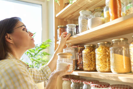 Food storage in pantry, woman holding jar of sugar in hand. Pantry interior, wooden shelf with food cans and kitchen utensils Foto de archivo